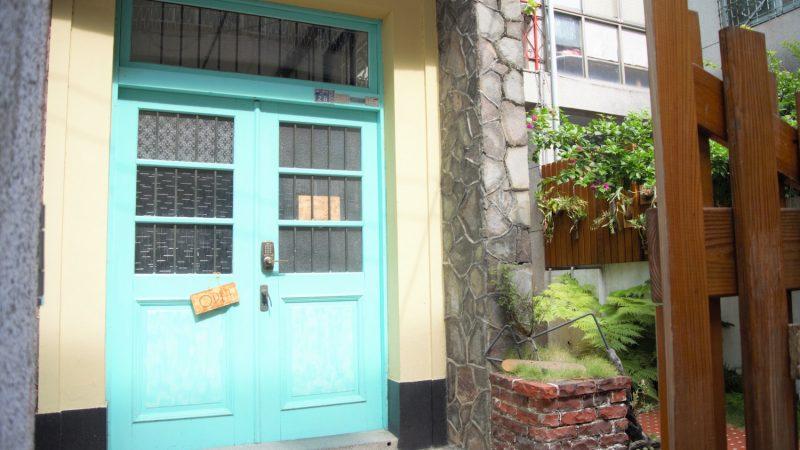「同・居 With Inn Hostel」のエメラルドグリーンに塗られたドア
